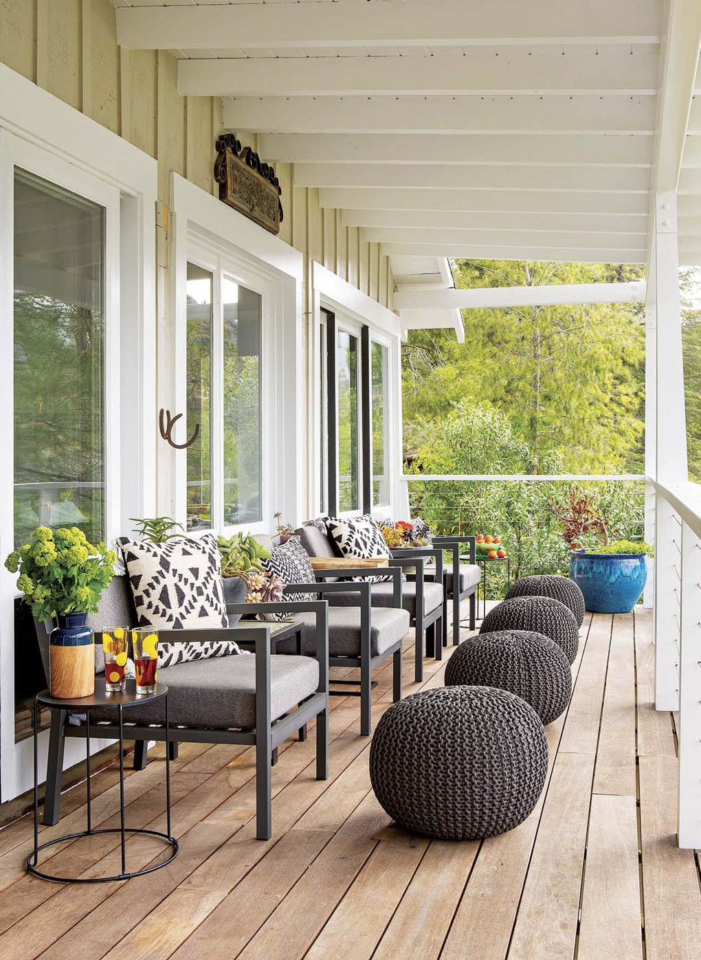 Lake house deck with wire railings in white and decorated with gray outdoor chairs and matching poufs as foot rests.