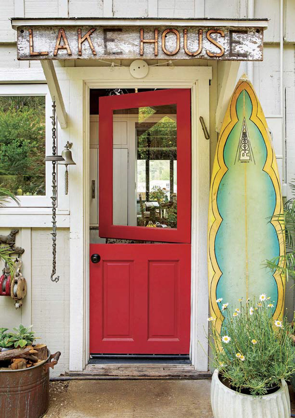 "Vintage sign that reads ""lake house"" placed above a bright red front door on a porch covered in lake house decor."