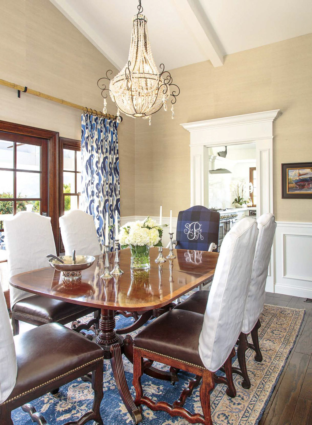 Regal British colonial formal dining space with a bright chandelier, double pedestal table and leather high-back chairs.