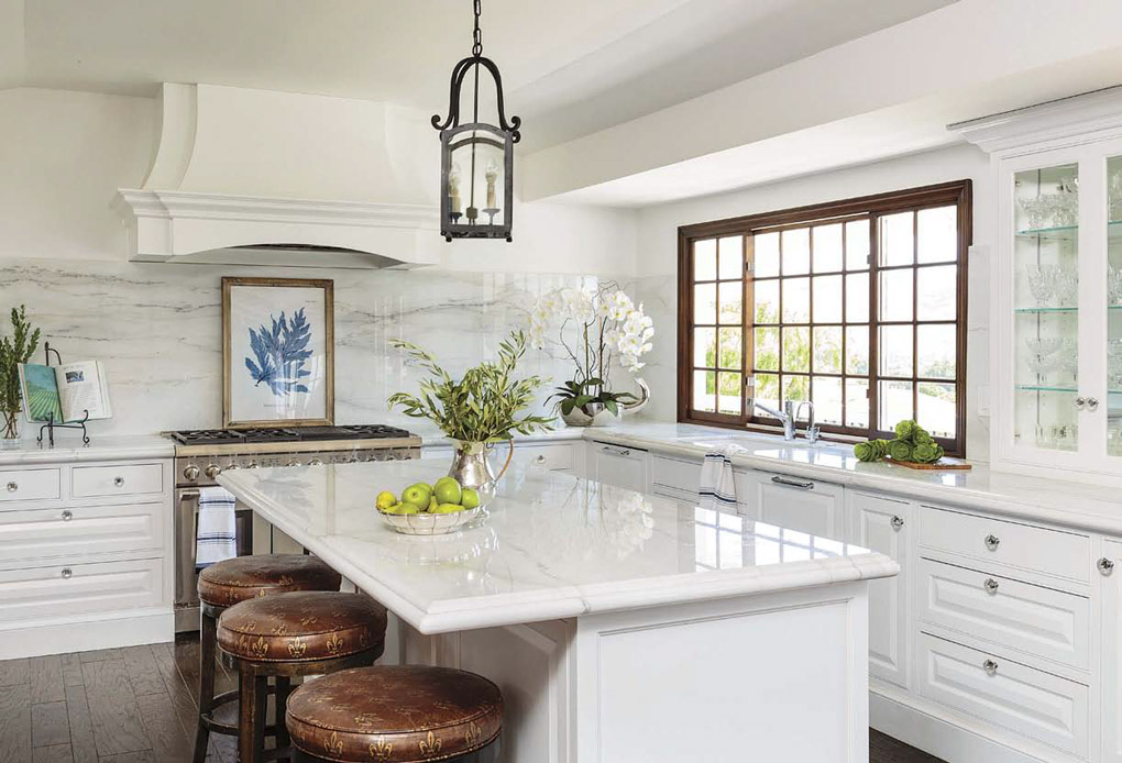 Welcoming home with an expansive all-white kitchen with marble counter and island tops and leather topped barstools.