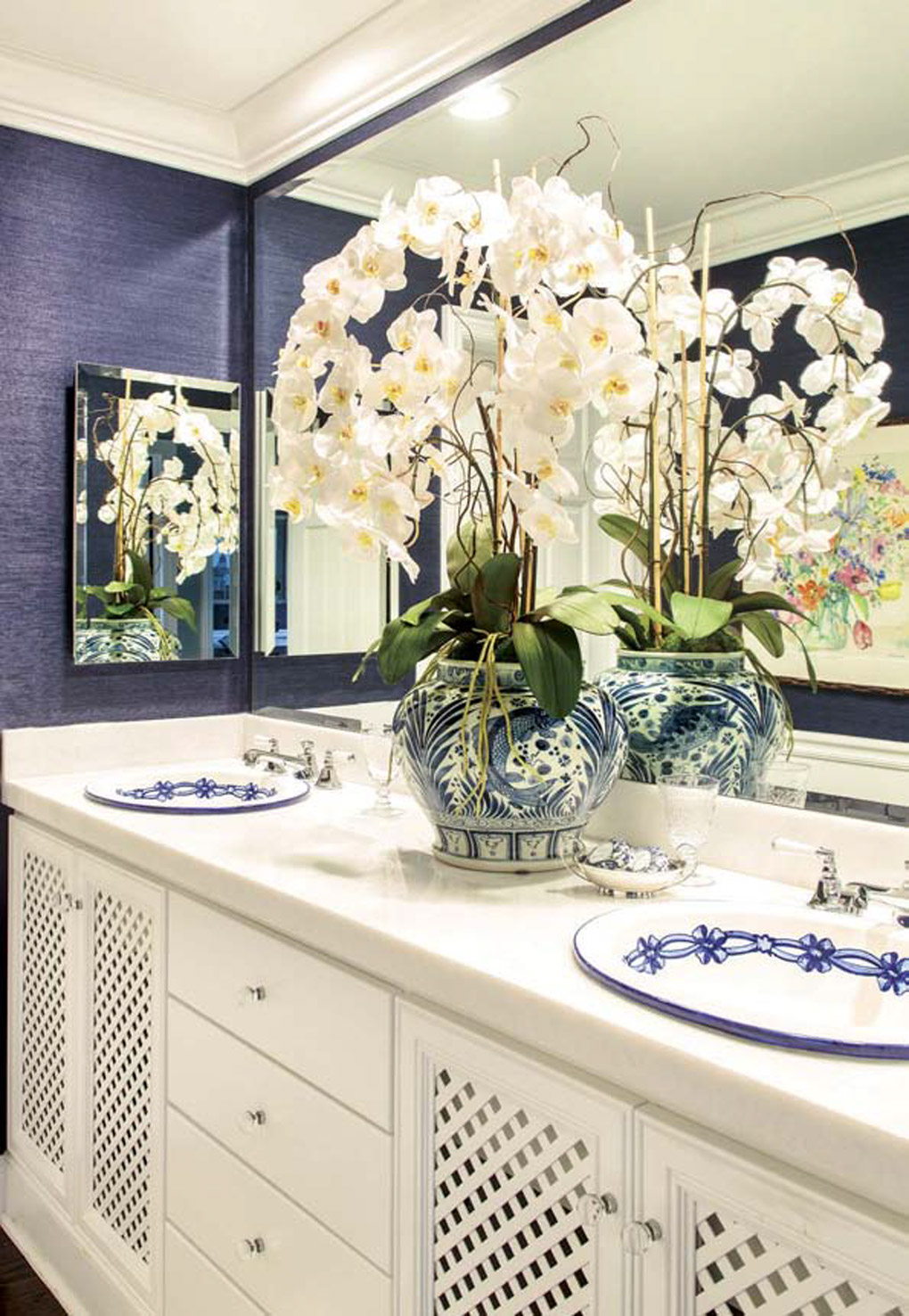 Blue and white Spanish sinks inlaid on a white double vanity in a bathroom topped with an oriental vase filled with white orchids.