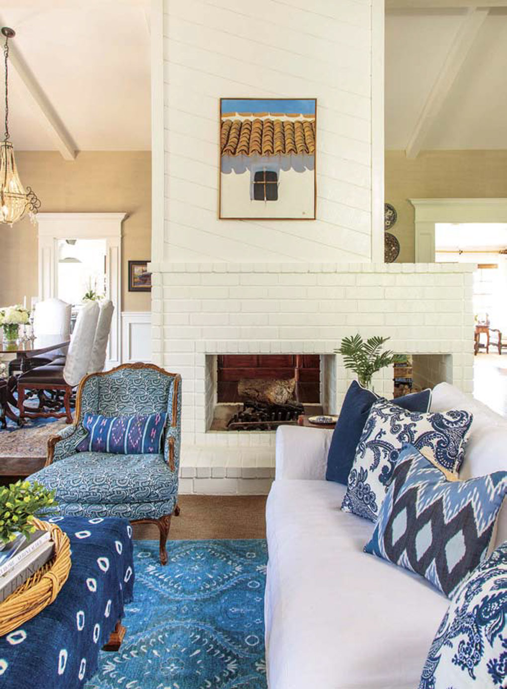 White, brick, walk-around fireplace, separating the dining from another seating area with blue rug, ottomoman and throw pillows accenting the white furniture.