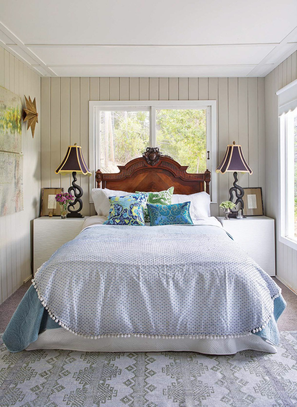 Master bedroom with 1940s vintage millwork around the walls and ceiling, light blue bedding and snake andirons turned lamps on the bedside tables.