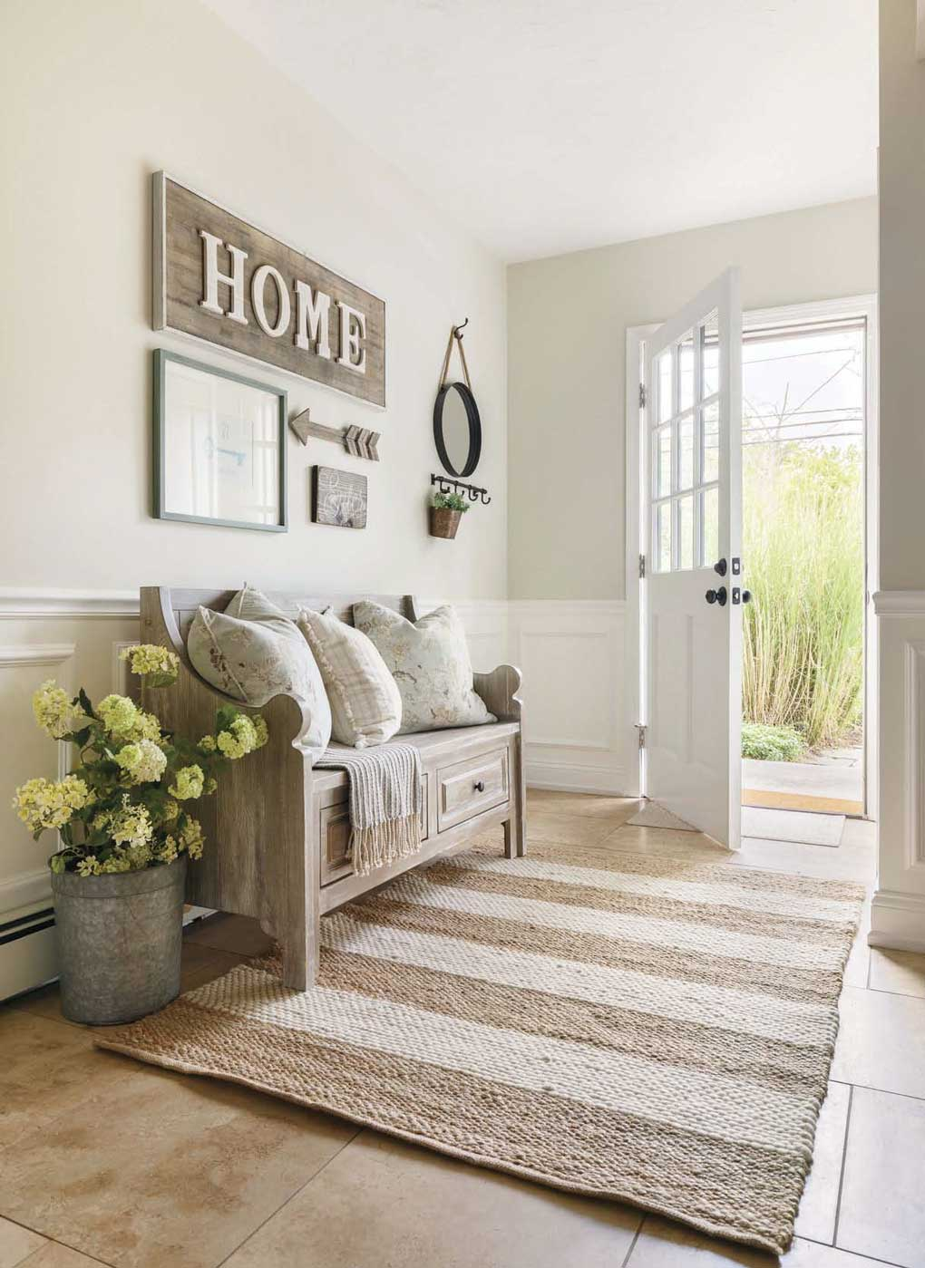"An open white door leading in to a casual mud room, with a light wooden bench, a wall sign that says ""home"". and a striped jute rug."