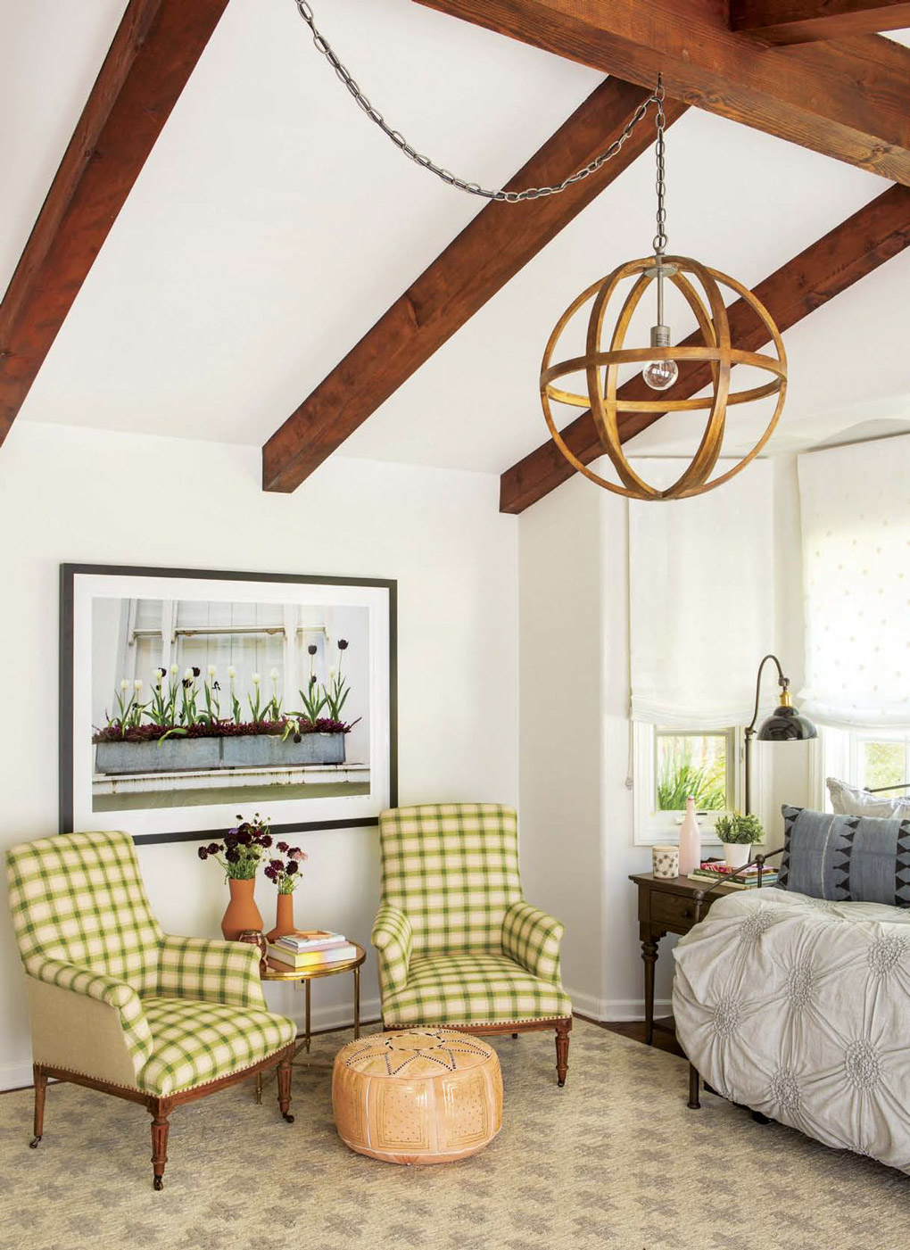 California cottage with bold exposed beams with a circular chandelier placed above green checkered armchairs.