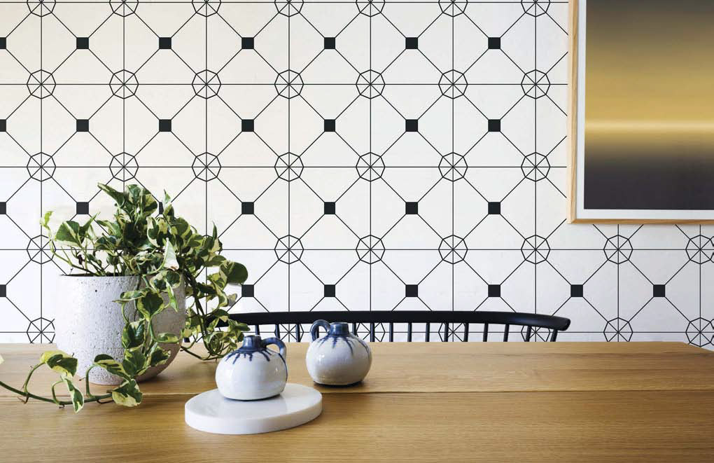 Wooden dining table with decorative salt and pepper shakers and potted plant showing off an accent wall with an intricate design of this self-adhesive wallpaper.