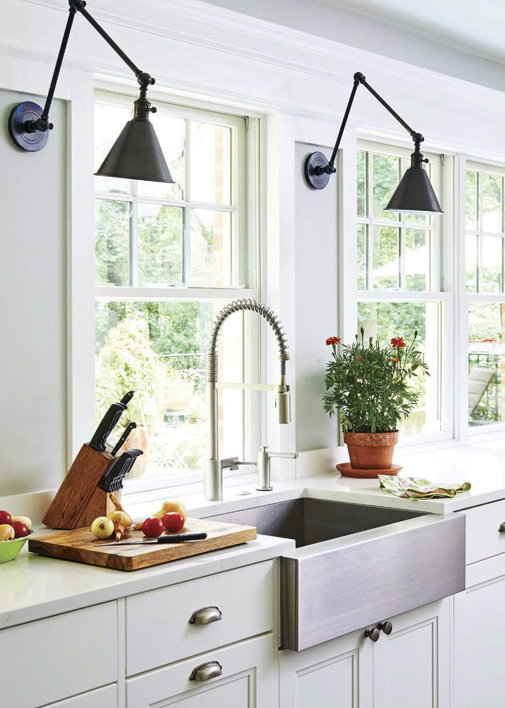 White kitchen with chrome farmhouse sink, chef's faucet and cutting board with fresh fruit.