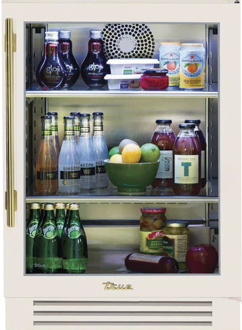 Undercounter beverage fridge in antique white with brass handle, filled with snacks and beverages.