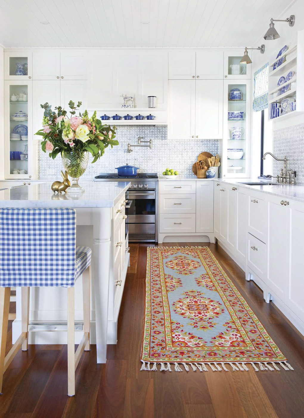 All white kitchen with cobalt blue accents and items in shelving, blue upholstered gingham bar stool and colorful floor runner.