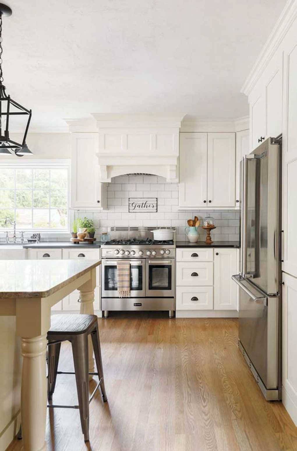White kitchen with rustic cabinetry, oil-rubbed bronze pendant lights above the island and stainless steel appliances.