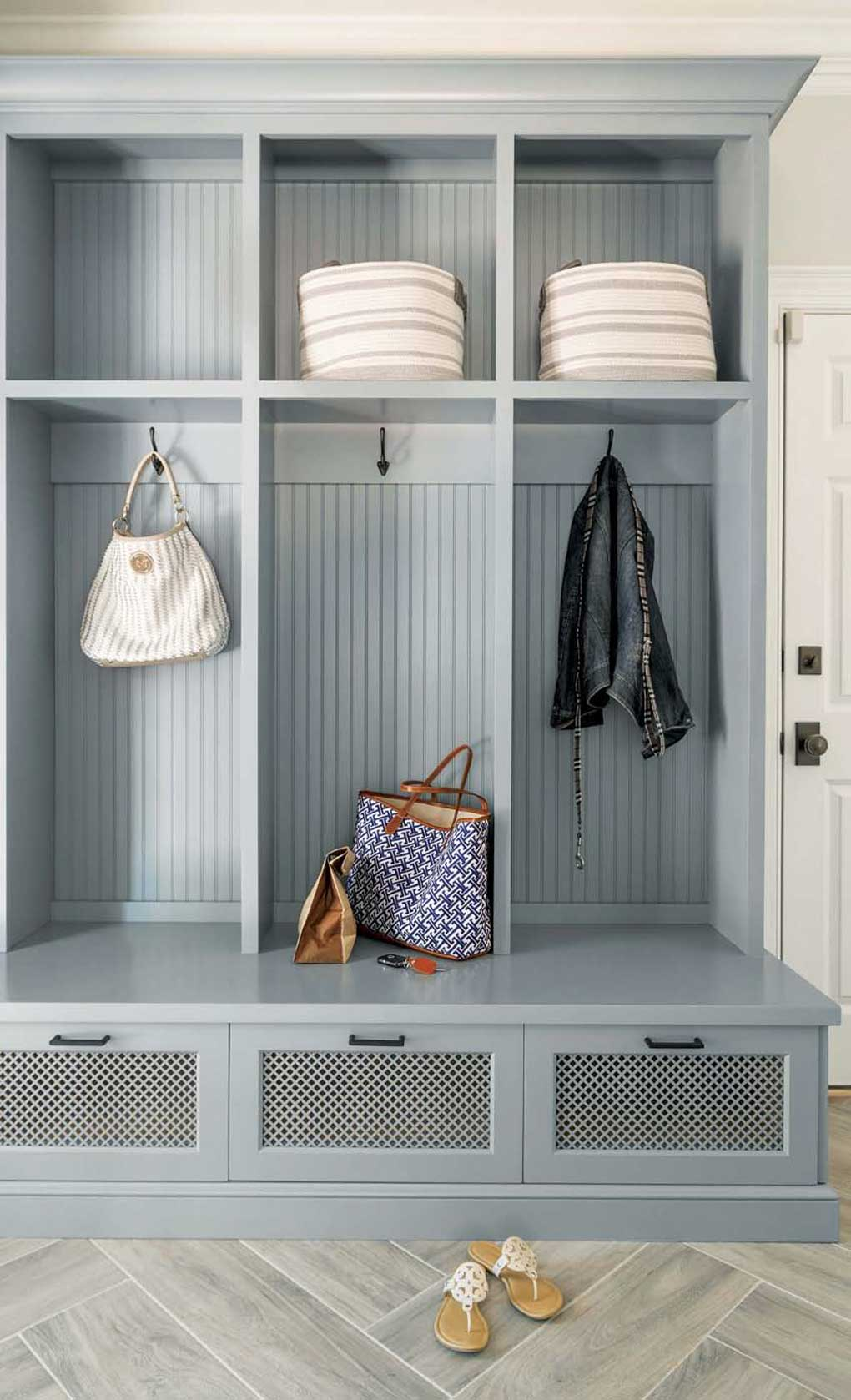 Gray blue colored builtin mudroom renovation with three separate personal spaces for folded, hanging and drawer items.