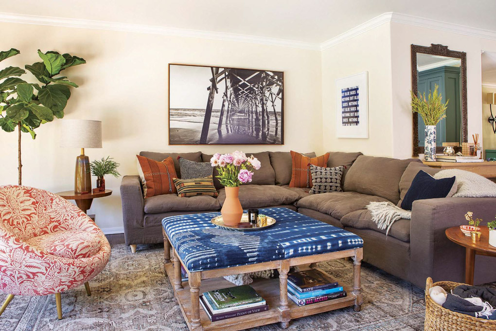 Wide shot of a living room in a California cottage with a floral barrel-back chair, sectional gray couch and a coffee table covered in Shibori fabric.