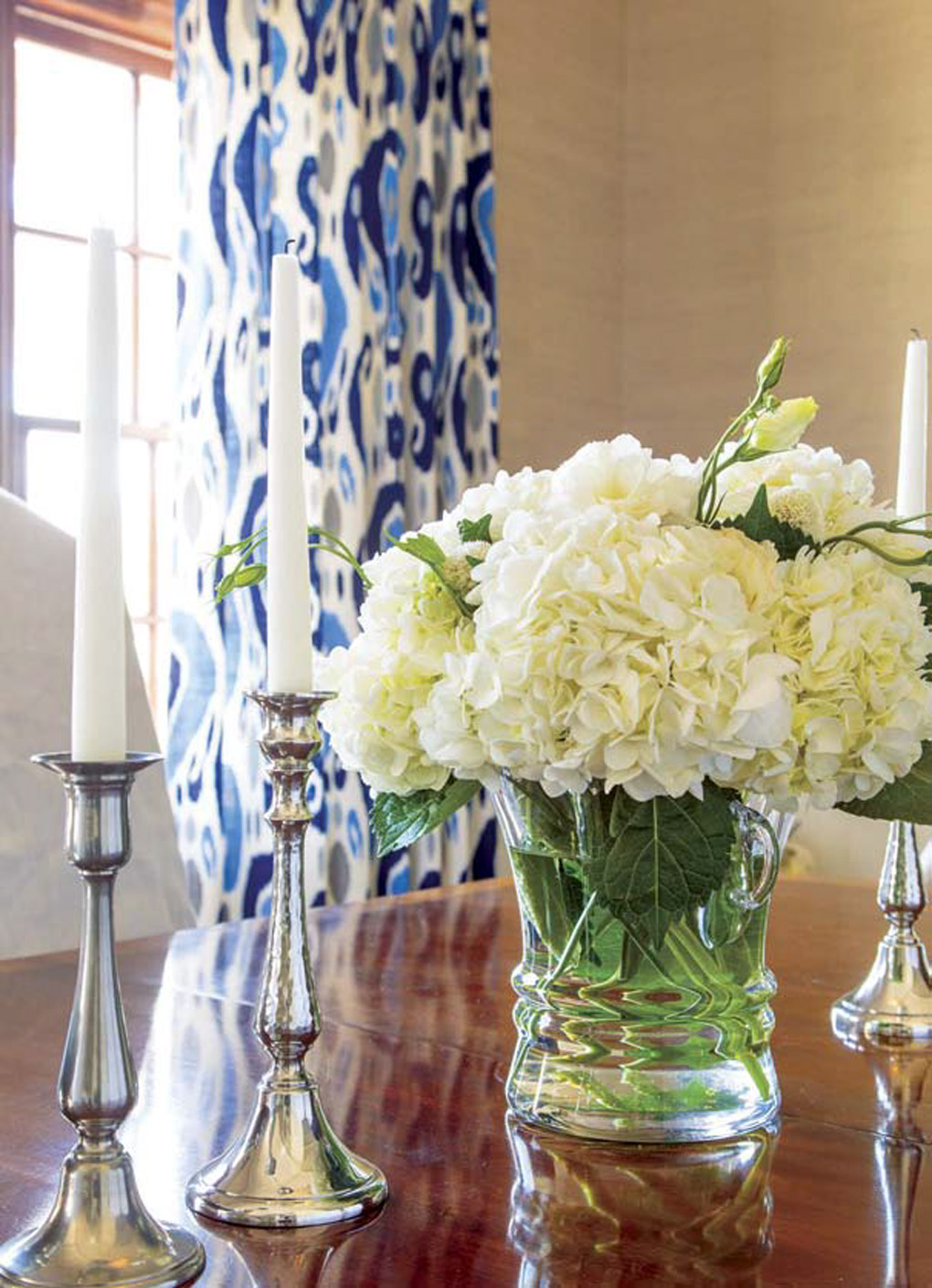 Full creamy hydrangea flowers in a clear vase on the table next to silver candlesticks on a wooden dining table with vibrant blue patterned curtains in the background.