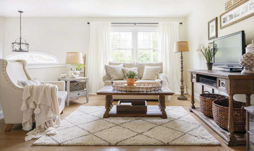 Bright and light neutral living room with oatmeal colored couch and armchair, wooden accent furniture and mercury glass lamp all on a light colored shag rug.