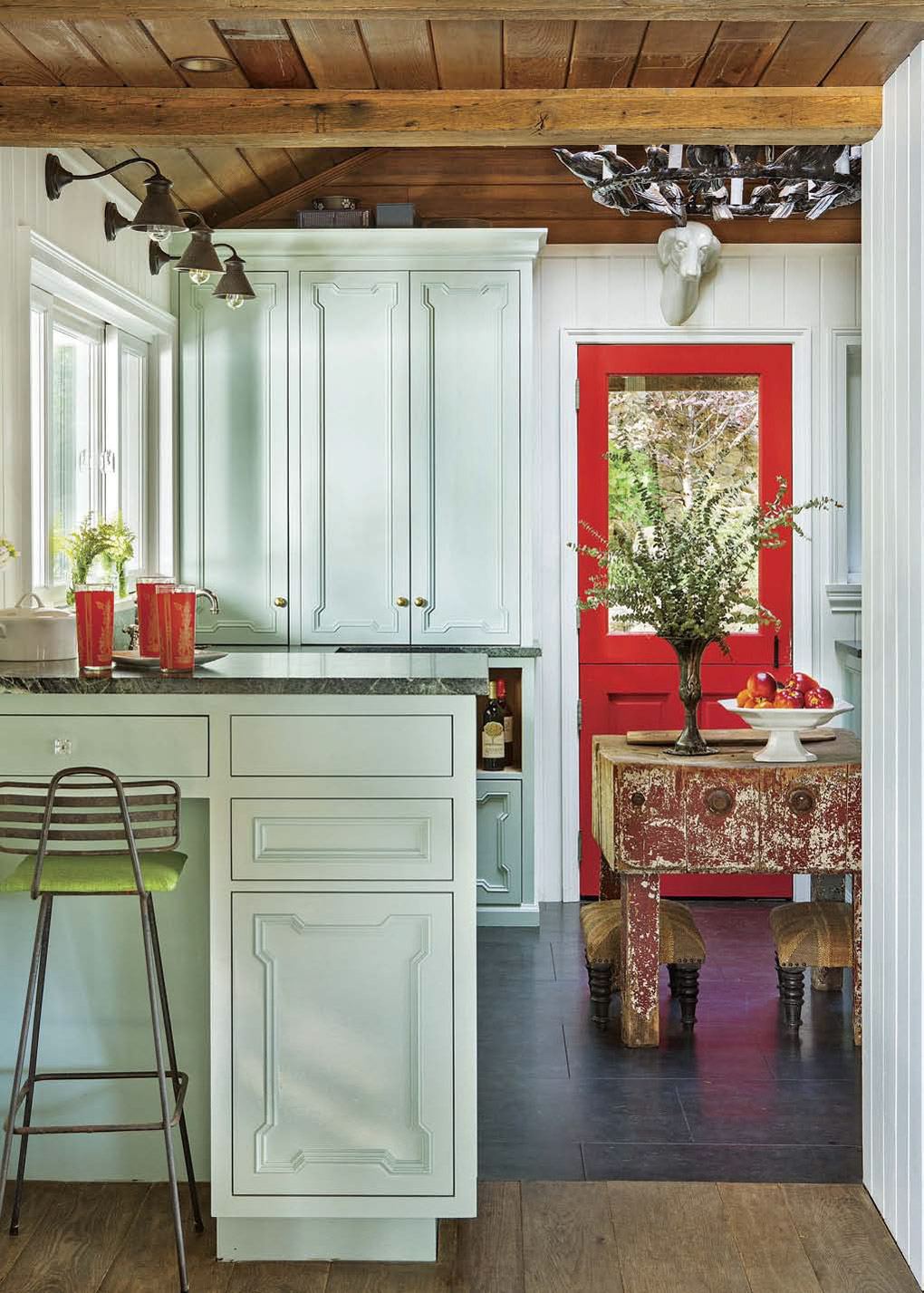 Light aqua cabinets in a kitchen with exposed beam ceilings and a bright red dutch door.
