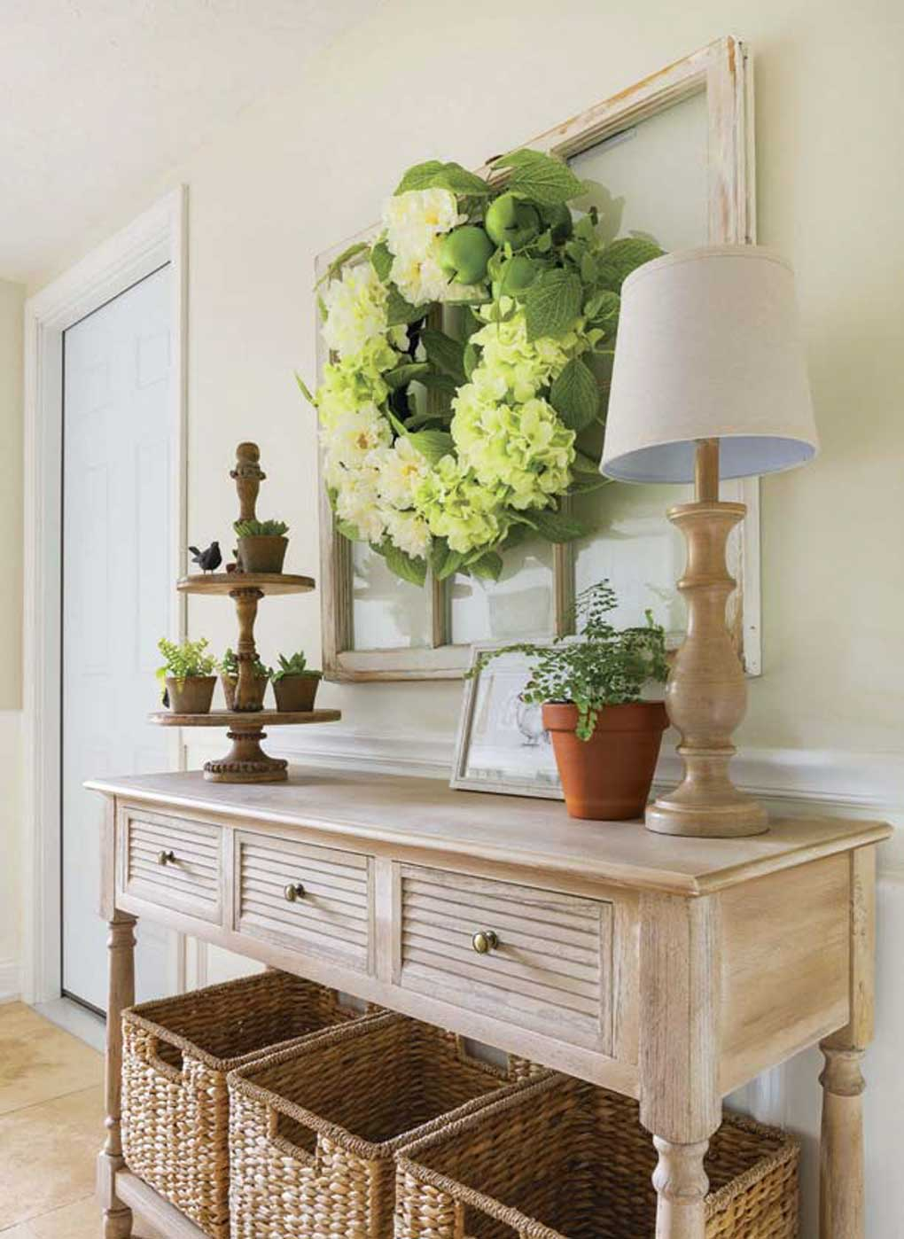 Entryway console table topped with plants and a lamp with three woven baskets underneath for storage as people enter the home and need to leave belongings.