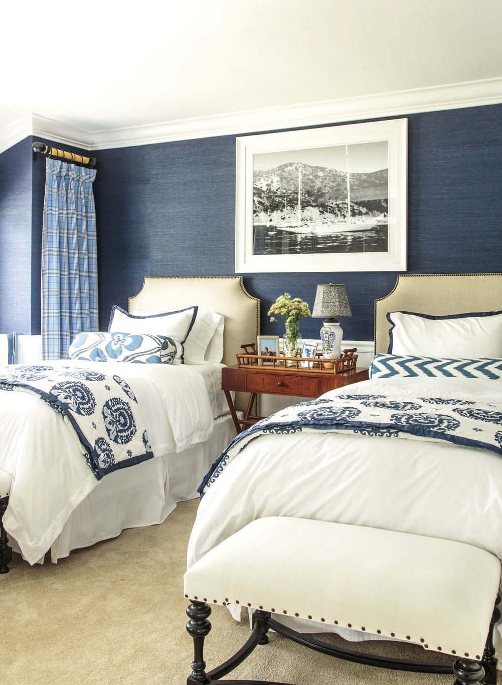 Regal British colonial style bedroom with two luxurious twin beds and blue linen textures walls.
