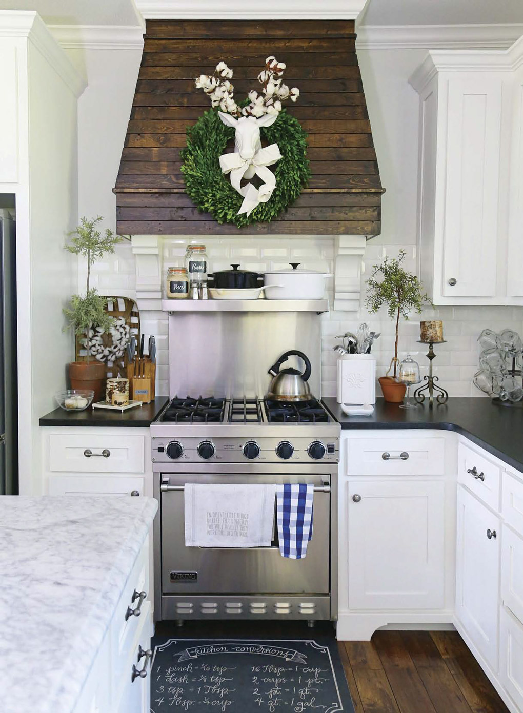 Kitchen with white cabinets and black countertops showing off a custom range hood with slatted wood and a bright green wreath with a white deer accent in the middle.