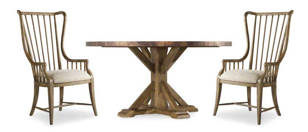 Farmhouse pedestal table and two high-back dining chairs.