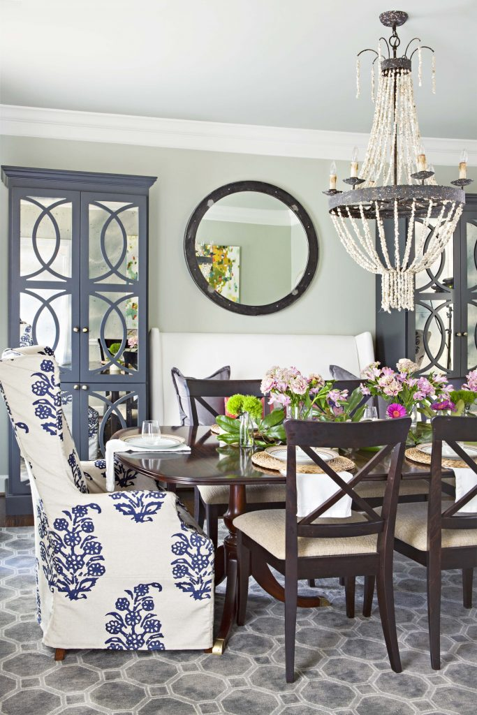 Regal cottage dining room filled with quality furniture like gray blue accents and pair of large detailed hutches in the background.