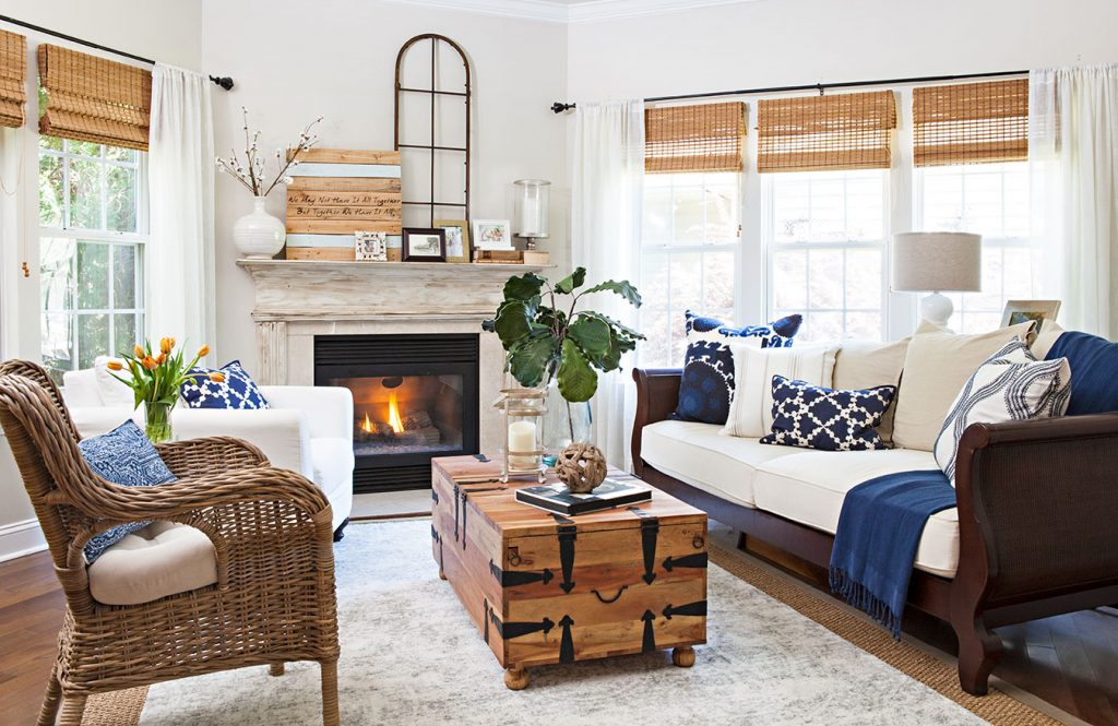 Rustic country cottage living room with whicker and wood furniture and cream and navy accents.