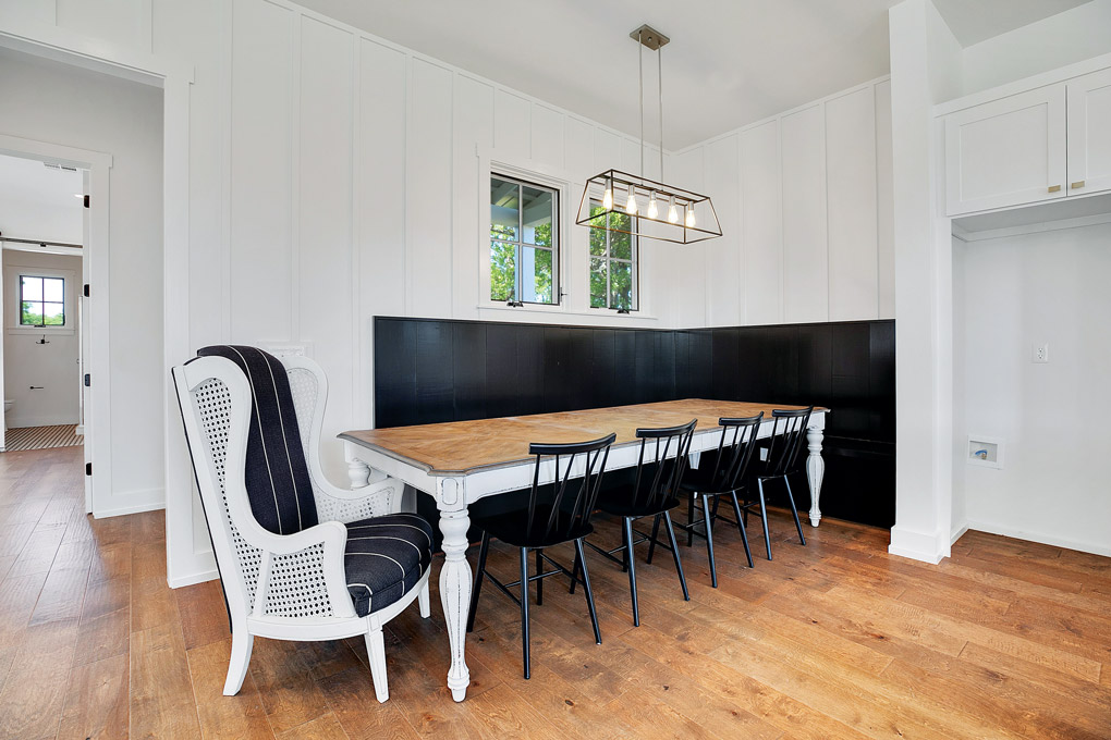 a black and white breakfast nook with a long far table and a wingback chair with cane panels.