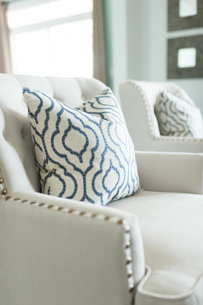 A pair of cream colored tufted armchairs with bolted arm details and a blue and cream throw pillow.