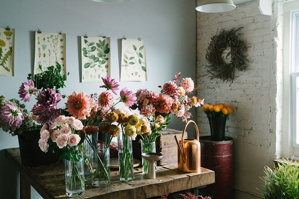 Floral design room with a wooden table covered in vases of flowers prepared to be placed in larger flower arrangements.