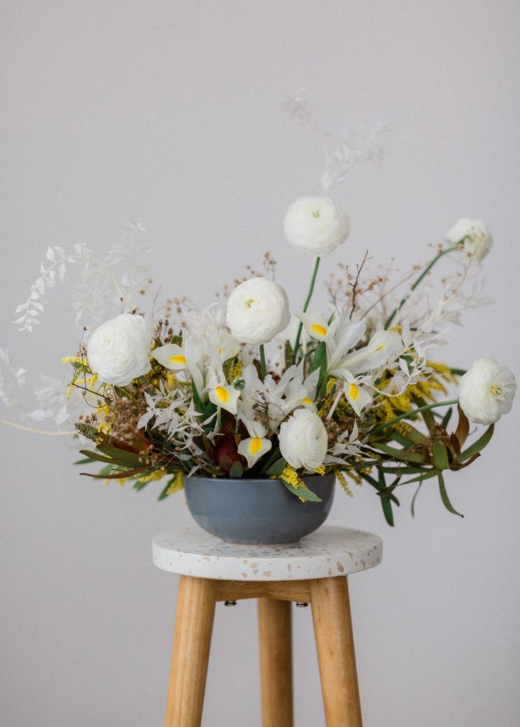 A Styled mid century modern floral design with a clean white wall with the flowers sitting on a simple stool
