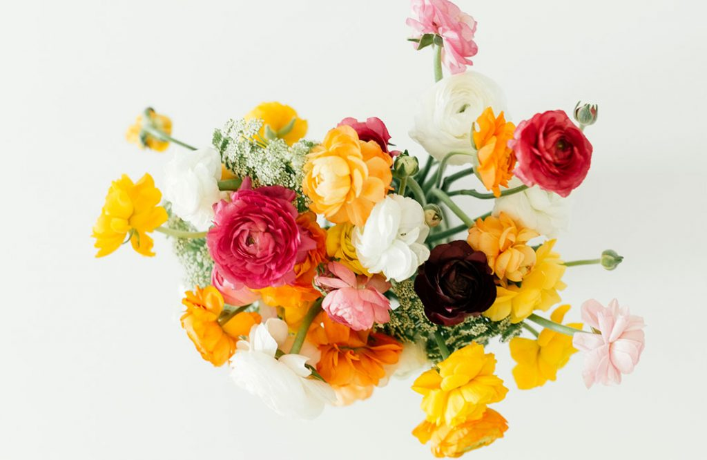 Overhead shot of a vibrant flower arrangement of peonies on a white table.