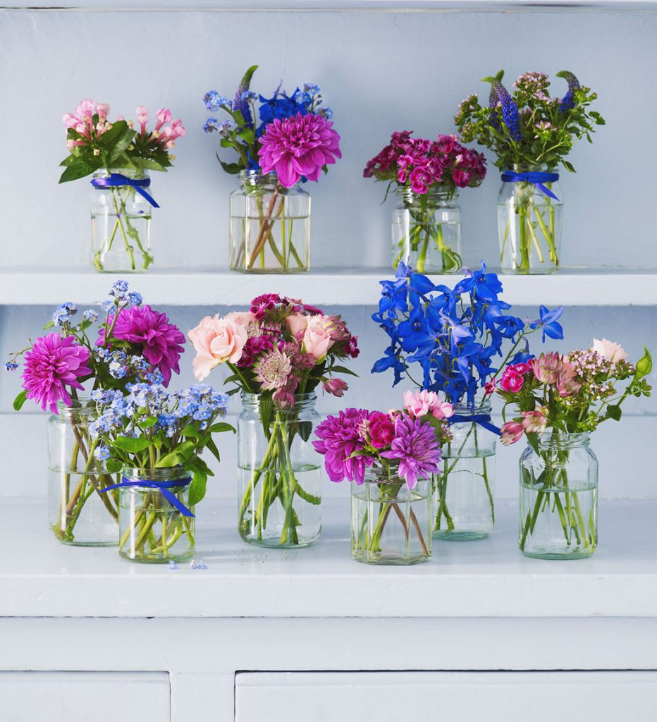 Clear glass jars tied with bright blue ribbons and filled with fresh flowers in shades of blue and pink.
