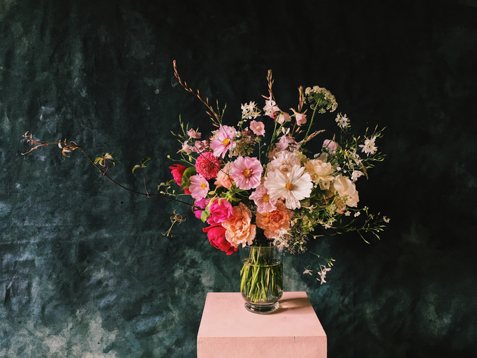 Dark backdrop with a tall pink box topped with a floral arrangement.