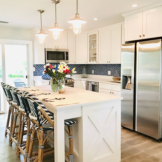 Modern farmhouse kitchen with a coastal vibe. White cabinets and stainless steel appliances with Parisian bistro woven barstools.