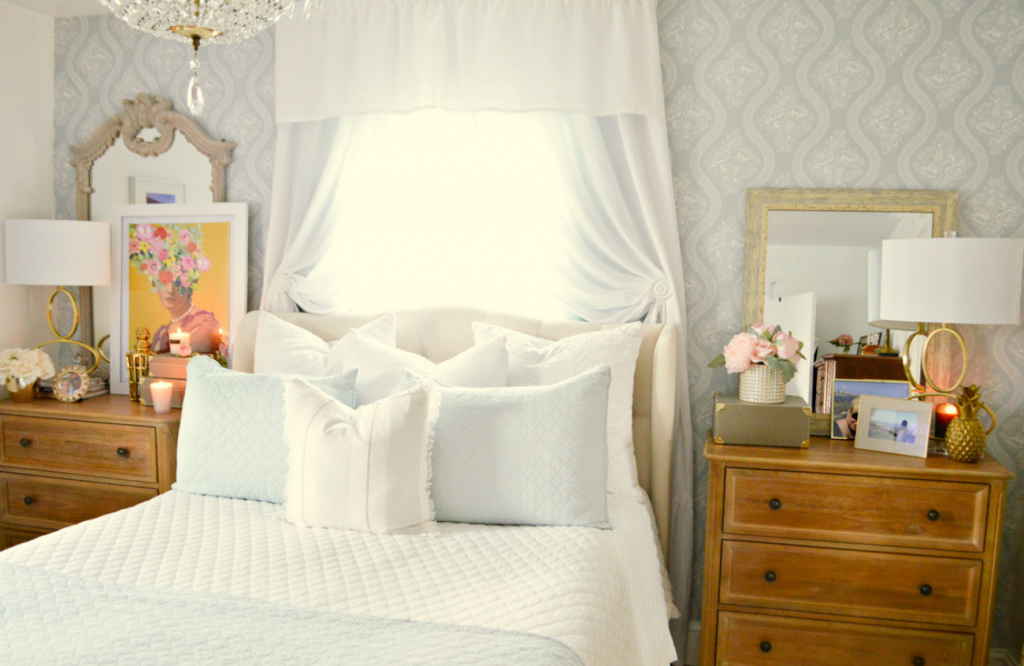 White and bright bedroom with pillows and window coverings flanked by two wooden dressers topped with art and lamps.