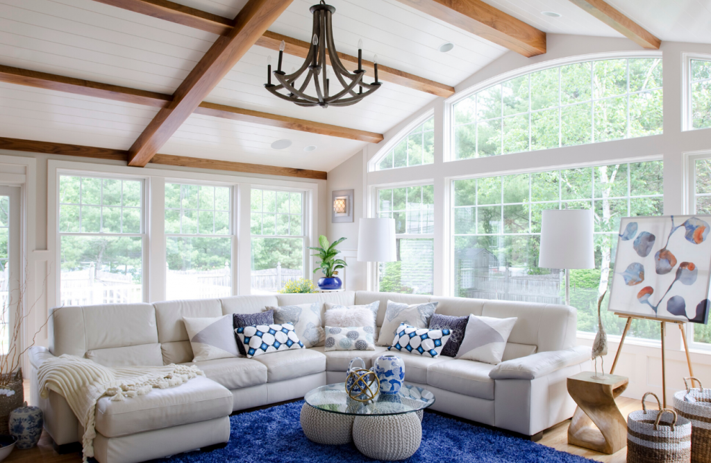 Modern cottage great room with exposed beams, classic blue rug and cream colored sectional surrounded by walls of windows.