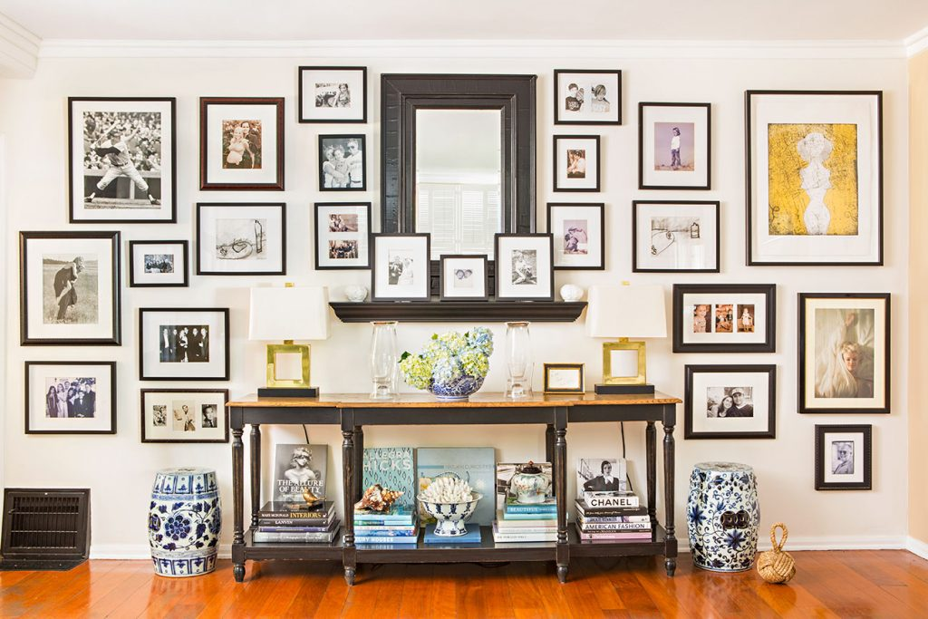 A dark console table against a large accent wall, covered with a large mirror, framed photographs and artwork.