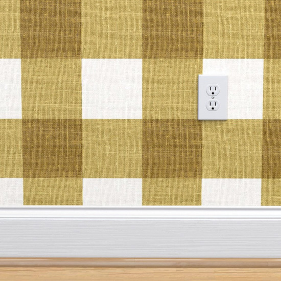 Gingham wallpaper white and mustard green color with white baseboards and white electrical outlet.
