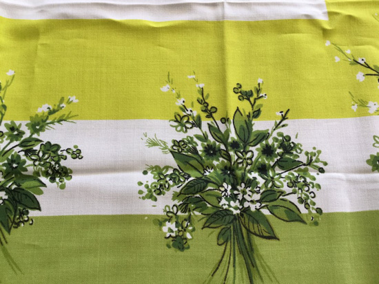 Vintage tablecloth pattern with shades of green and florals.