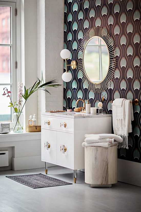 Modern styled bathroom with Art Deco patterned wallpaper under a sunburst mirror with white furniture.