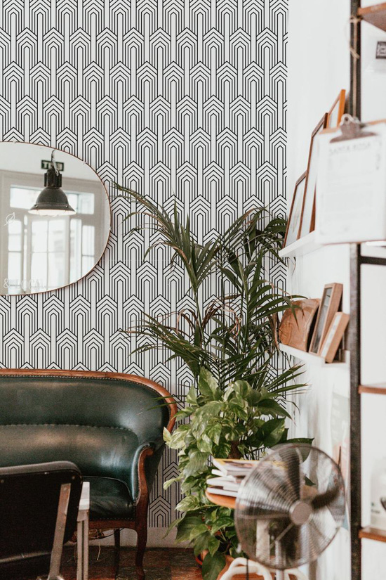 Art Deco patterned black and white wall paper in a study with bookshelves, large plant and leather couch.