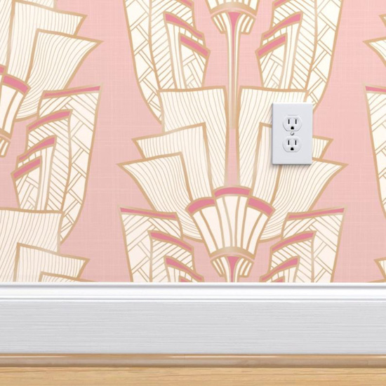 Pink Art Deco inspired wallpaper on a small patch of wall with white baseboards and a white electrical outlet.