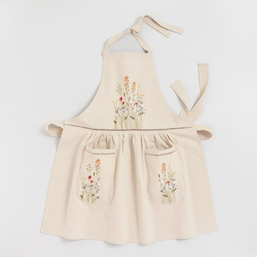 Natural cream colored embroidered floral apron with lace trim.