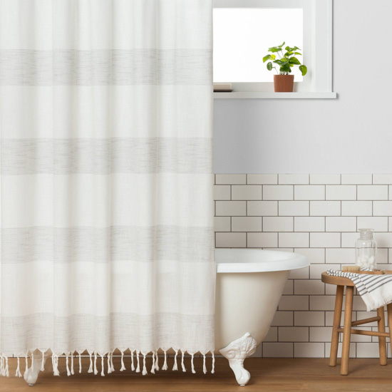 White clawfoot tub under a window, displaying a light striped woven shower curtain.