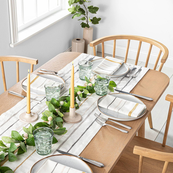 Light colored wooden table and chairs set for a meal with light colored table runner topped with yellow candles and fresh green garland.