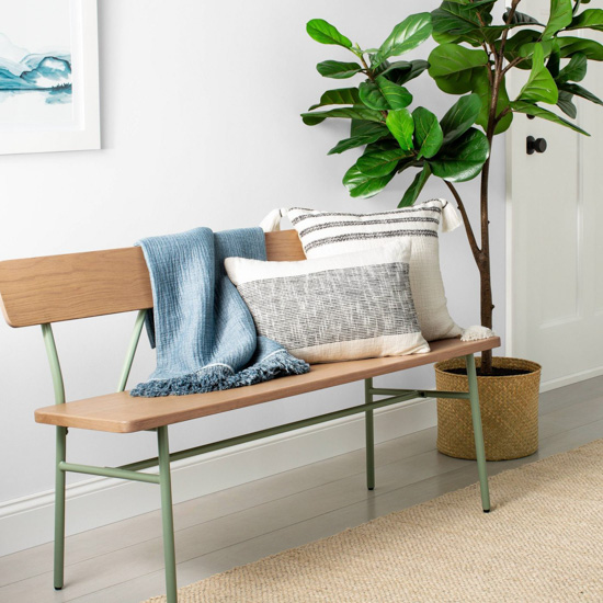 Green metal and wooden bench topped with a blue throw blanket and light colored pillows next to a fiddle leaf fig tree.