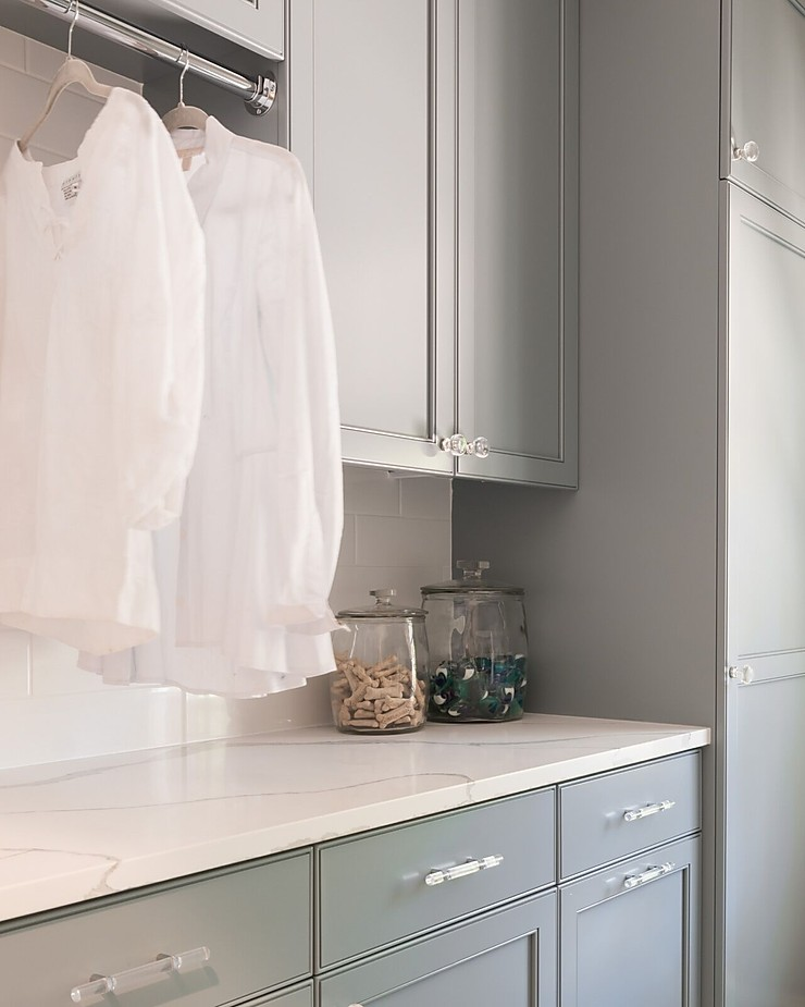 Light blue gray cabinetry with white marble countertop and white shirts hanging to dry.