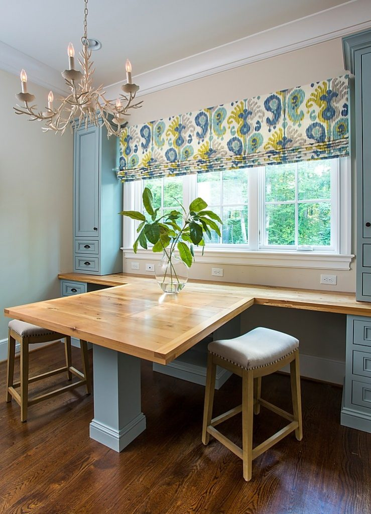 Shared desk space in a home office, with upholstered stools and a white chandelier and blue cabinetry.