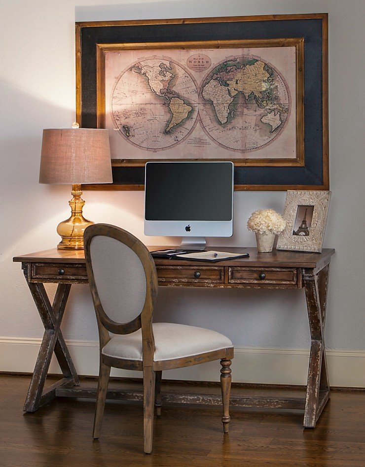Intimate home office space with apple desktop computer, wooden desk and chair and framed and matted atlas print hanging above it.