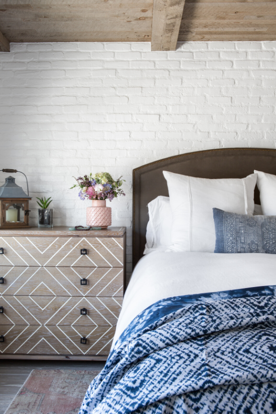 White brick wall and exposed wooden beam ceiling in a bedroom with a wooden dresser and a blue shibori comforter at the foot of the bed.