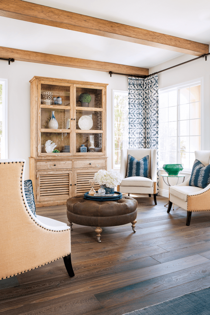 tall cottage sitting room with exposed beams, 4 slipper chairs a round tufted ottoman and a tall china cabinet in knotty pine